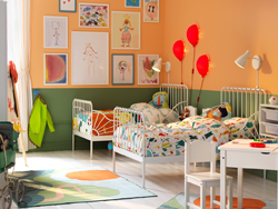 Children's bedroom with two white, extendable beds, writing table and chair. Walls painted in green and orange.