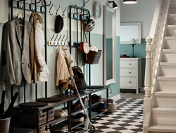 Traditional hallway with black and white chequered floor and two black coat racks and shoe storage benches side by side.