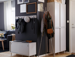 A dark grey open hallway with white storage units and coat hooks.