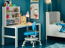 A blue children's room with a white desk and bed and blue and white swivel chair.