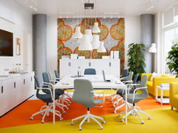 A bright yellow, orange conference room with white table and blue and light green swivel chairs.