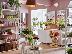 Flower shop with pink walls and white wall shelving units.
