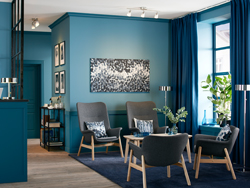 Waiting room with four dark grey armchairs in a blue office reception area.