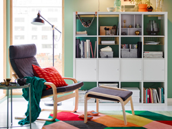 A green and grey reading corner with multi-coloured rug and white shelving units.