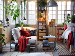 A relaxed living room with white sofa with books and other stuff on a built-in shelf beneath, jute rugs and plants.