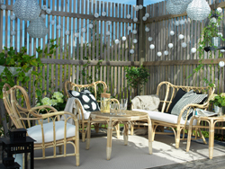 A covered terrace with rattan sofa, coffee table, armchair and side table.