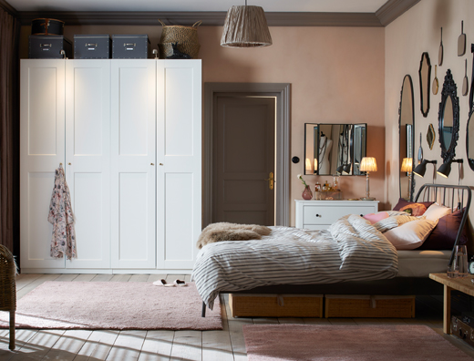 A traditional style bedroom in dusty pink and light grey with two white wardrobes side by side.