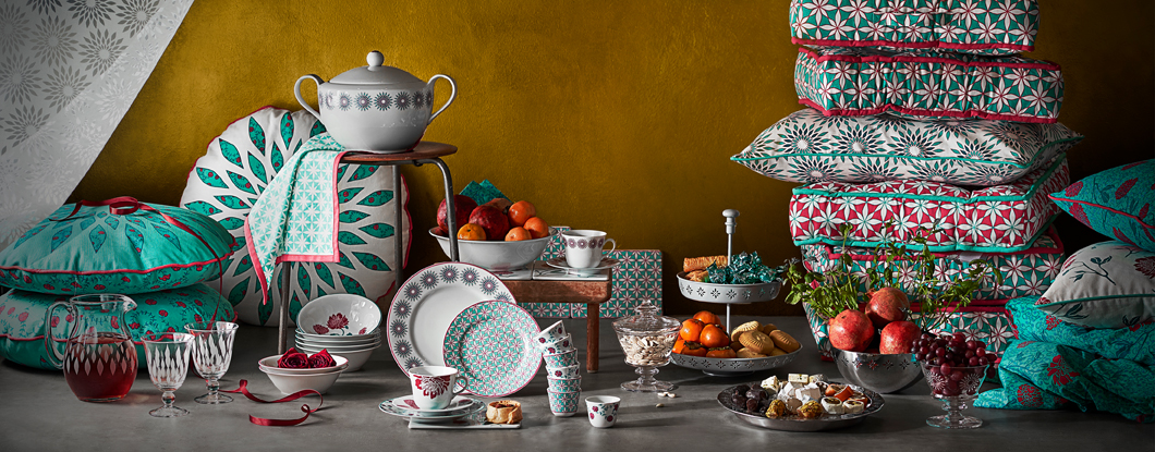 Display of a collection consisting of tableware in feldspar porcelain with different floral patterns, textiles with floral or geometric patterns in turquoise, red and white and glassware with a geometric pattern.