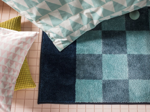 Close-up of a dark blue and turquoise chequered rug with thick soft pile.