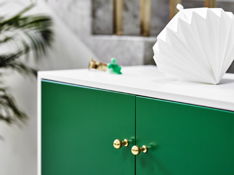 Close-up of a white cabinet with green doors and round brass-coloured knobs.