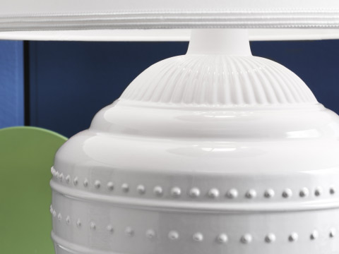 Close-up of a white stoneware lamp base with embossed pattern