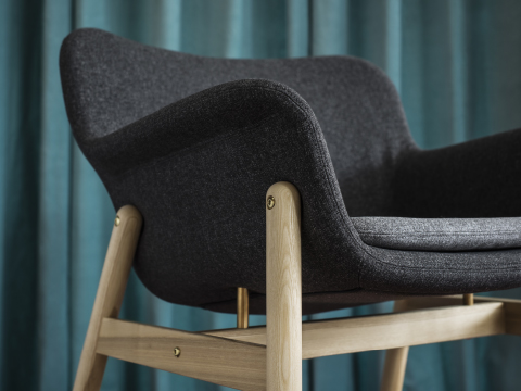 Close-up of an ergonomic designed armchair with a grey cover and clear lacquered solid ash legs.