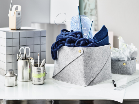 A white desk with a grey felt basket with blue wool yarn and knitting needles inside. Shown together with a smaller felt basket with paper napkins.