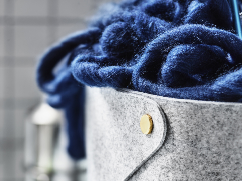 Close-up of a grey felt basket with blue wool yarn inside.