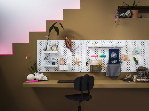 A home office with several white pegboards shown together with accessories in white lacquered steel, such as a shelf, containers, clips, hooks, roll holder and letter holder.