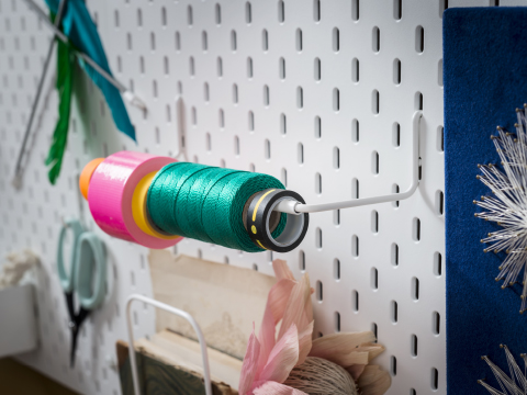 Close-up of a white pegboard featuring a roll holder with tape in different colours and a roll of green sewing thread. Underneath a letter holder with an old book and a pink artificial flower.