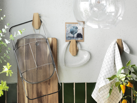 A kitchen wall with large bamboo hooks in an irregular hexagonal shape, one hook shown with a chopping board and a colander and one hook with a tea towel.