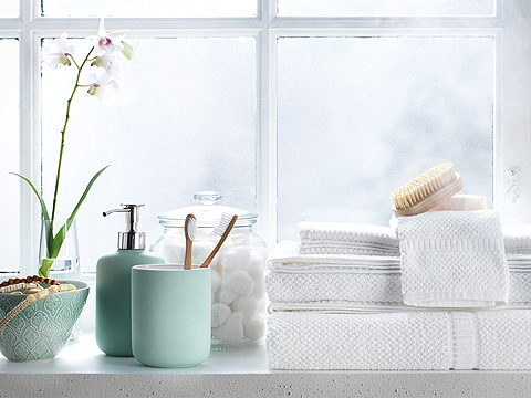 Light green soap dispenser, toothbrush cup and white towels along windowsill.