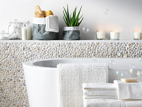 Candlelit bathtub with white mat, towels and aloe vera plant.