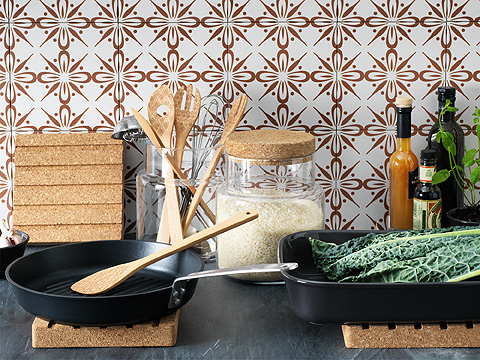 Grey kitchen work surface with frying pan and baking tray in front of jars containing ingredients and wooden utensils.