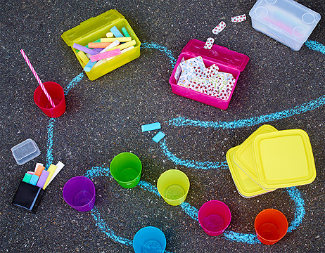 Outdoor play with chalk and colourful plastic cups on asphalt.