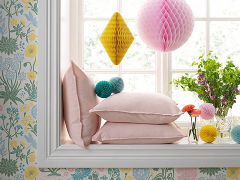 Cushions and hanging paper pom-poms decorating a window.