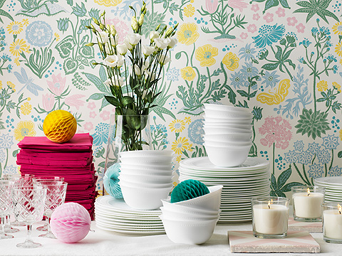 Colourful paper pom-poms and stacked white dinnerware on candlelit table.