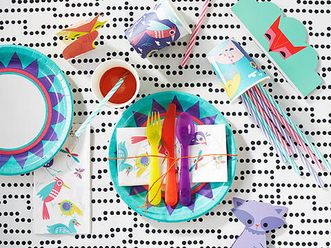Colourful cutlery set for kids on black and white graphic table runner.