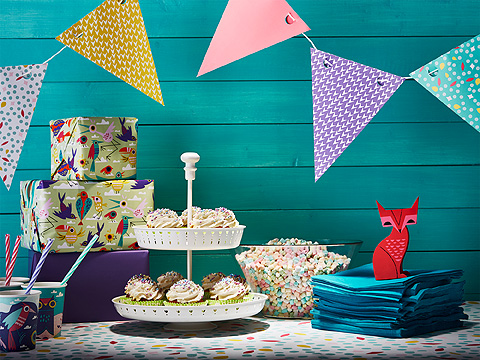 Colourful bunting over table with 2-tier cake stand, cups with straw and napkins against a turquoise background.