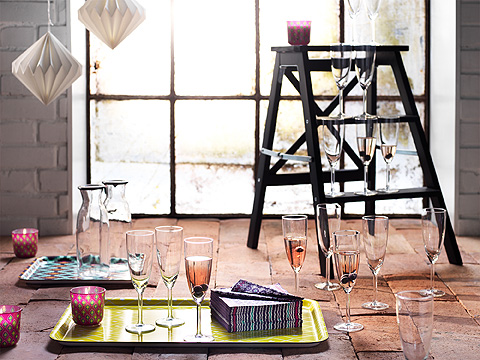 Candles and champagne glasses on colourful trays on brick floor.