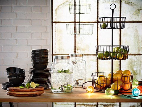 Table with stacked dinnerware, 3-tier serving basket stand and glass water dispenser.