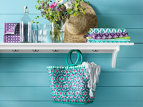 Green bag hanging on white shelving unit with straw hat, vase and glassware against a turquoise wall.