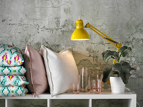 White shelving unit with cushions, a bright yellow lamp, glassware and a plant.