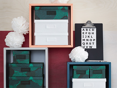 Assorted white and green storage boxes stacked inside shelving units with paper pom-poms.