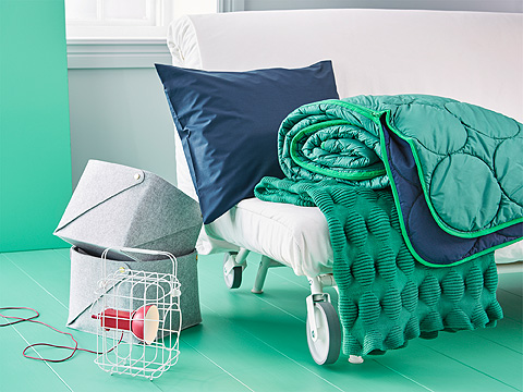 White roller sofa bed with blue cushion, green throw and blue and green sleeping bag.