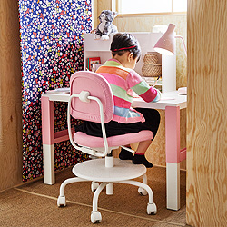 A girl sitting on a white/pink swivel chair by a white/pink height adjustable desk doing her homework.