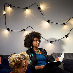 A girl sitting in a sofa reading a book and on the wall behind the sofa hangs a lighting chain with clear light bulbs.