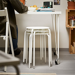 A stack of white stools under a desk.
