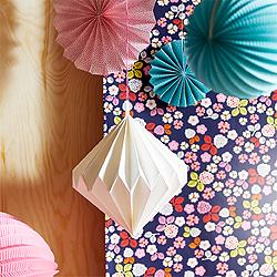 Close-up of hanging paper decorations in white, pink and turquoise.