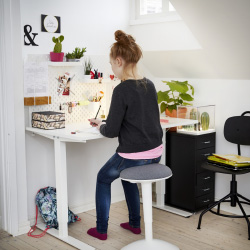 A girl sitting on a standing support by a white height adjustable desk doing her homework.