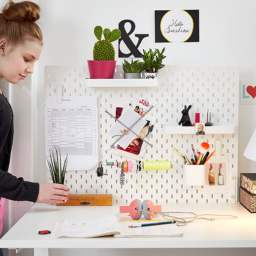 A white peg board featuring shelves with small plants, containers with pens and clips with a timetable.
