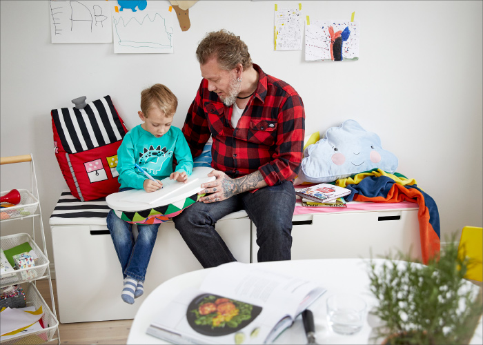 A man and his son sitting on a white storage bench reading a book.