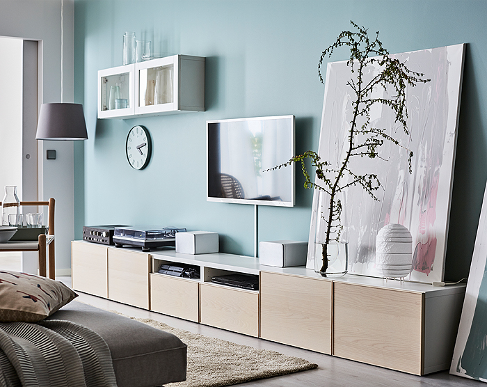 TV media storage unit in walnut and white in a bright turquoise blue room.