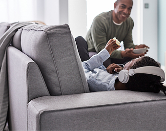 IKEA KIVIK spacious sofa with chaise lounge makes room for the whole family to socialize, for example children listening to music and parents having a snack.