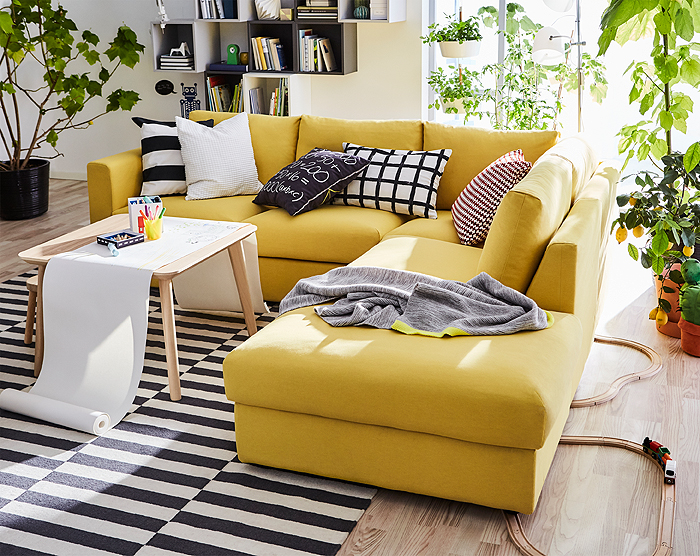 Golden yellow sectional sofa with patterned cushions in a bright and green space.