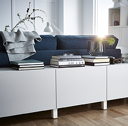 Small, modular storage combinations can fit almost everywhere, like behind a sofa. This white BESTÅ storage combination with light grey, knob-free drawer fronts devours living room clutter, and becomes a decorative side-table for books and magazines.