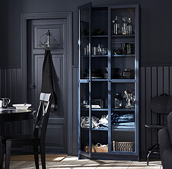 A tall BILLY bookcase makes the most of your wall height instead of using precious floor space. It also becomes a home for wine glasses, blankets, a coffee pot and more. The dark blue colour and the glass doors make a fresh, modern style statement.