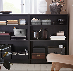 Creating extra storage with low BILLY bookcases with shallow shelves is simple – they can even be placed in unused spaces between rooms, or under a window. Black-brown natural wood veneer makes for a perfect frame for displaying beautiful books and boxes.