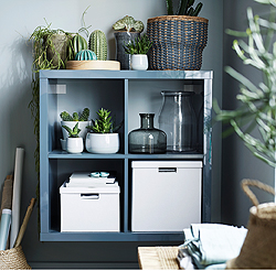 A KALLAX shelving unit with clean, simple design can create stylish additional storage and display in small and unused spaces. The high-gloss grey-turquoise surface is a beautiful backdrop for green plants, grey glass vases and white cardboard boxes.