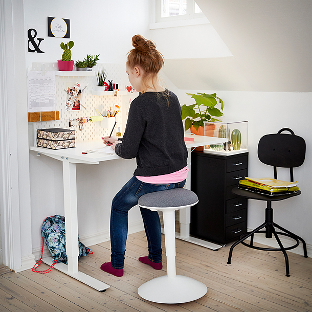 support by a white height adjustable desk doing her homework.